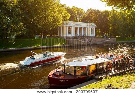 ST PETERSBURG RUSSIA - AUGUST 15 2017. Rossi Pavilion in the Michael Garden and the Moika river with floating pleasure boats in St Petersburg Russia. St Petersburg Russia city summer view