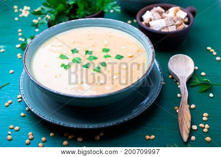 Pea Soup In Green Bowl On Green Wooden Background. Dry Yellow Pea. Vegan Food.