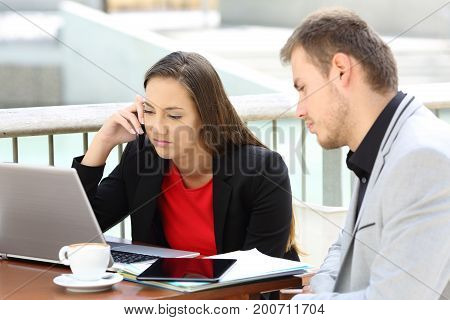 Two frustrated executives working sitting in a coffee shop outdoors