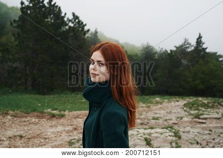 Beautiful young woman walking in the mountains near the forest.