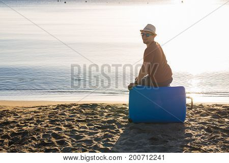 Man in sunglasses with luggage on the sea in summer sunny day.