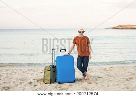 Young caucasian tourist man is standing alone on the beach with a suitcase