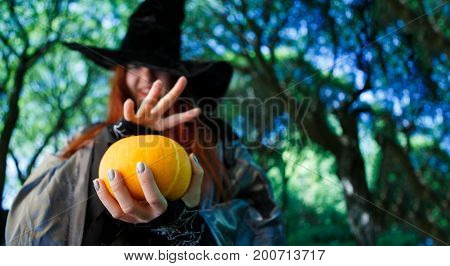 Photo of witch with pumpkin reading spells in night park