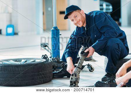 Automechanic Holding Car Part