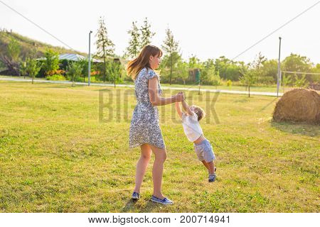 happy family having fun. baby boy and his mother playing outdoors.