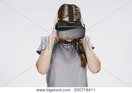 Beautiful young woman on white isolated background in virtual reality glasses.