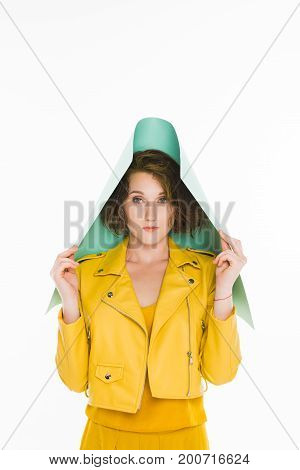 fashion portrait of young girl in yellow leather jacket covering head with turquoise paper isolated on white