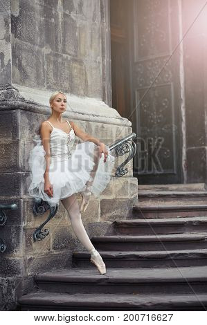 Portrait of a beautiful young blonde ballerina in white outfit standing gracefully on the stairs of an old castle.