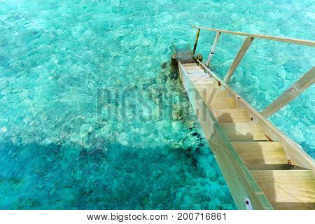 Ladder to crystal clear turquoise sea in tropical Maldives island