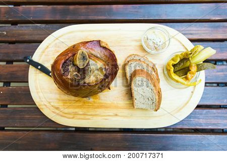 Roasted pork knuckle eisbein with bread and vegetables on wooden cutting board, top view.