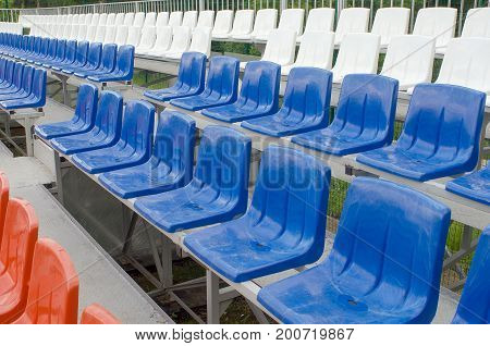 Five rows of seats: grandstand at the outdoor Playground plastic seat red blue and white.