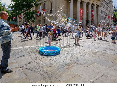 Trafalgar Square London UK - July 21 2017: Street entertainer making bubbles. Lots of people and children watching.