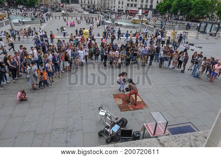 Trafalgar Square London UK - July 21 2017: Street performer with large crowd watching.Taken from the National Portrait Gallery and shows a lady putting money in his top hat.