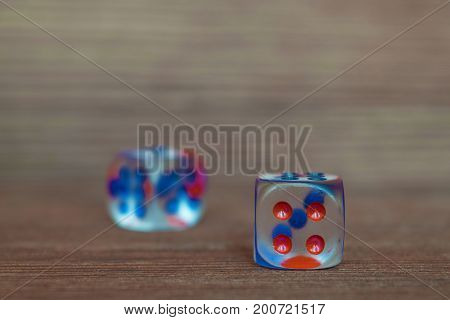 Two transparent dices on wooden board. Six sides with blue and red points. Artistic blurring.