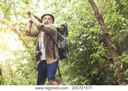 Crazy old man is beating off by wooden stick and looking forward with panic. He is standing in forest and carrying touristic backpack. Copy space