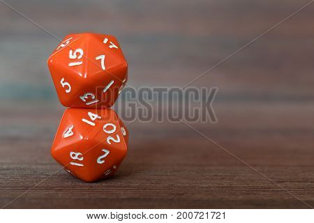 Two red dices on each other on wooden board. Twenty sides with white numbers.
