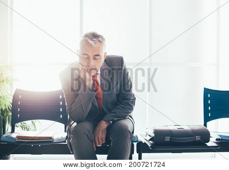 Tired Businessman Sleeping In The Waiting Room