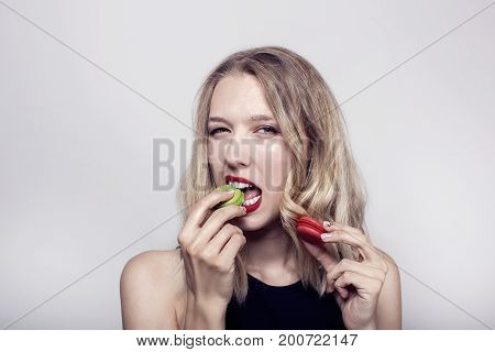 Funny cute young girl with light long hair gaily eating macaroons