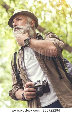 Low angle of thoughtful senior man standing in forest with touristic backpack. He is holding retro camera and ready to take a photo