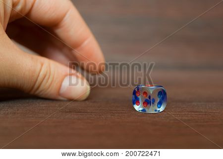 Woman hand taking transparent dice from brown wooden board. Six sides with blue and red points. Blurry background.