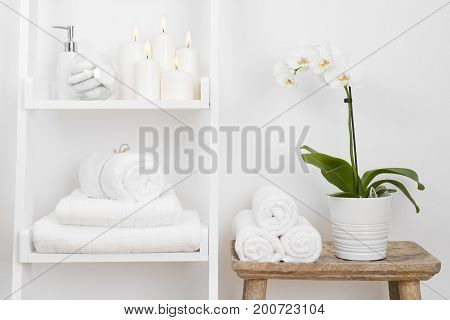 Shelf with clean towels candles flowerpot on bathroom wooden table