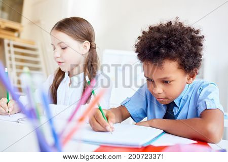 Diligent pupil with pencil drawing something in copybook with classmate near by