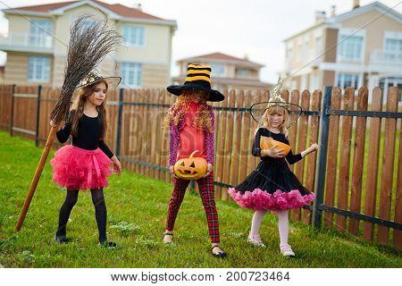 Trick-or-treat girls walking down green grass along wooden fence
