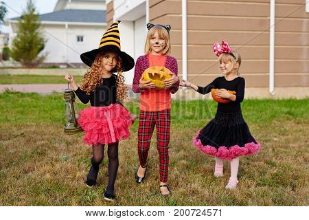 Halloween kids with treats walking down lawn in the yard after trick-or-treat fun