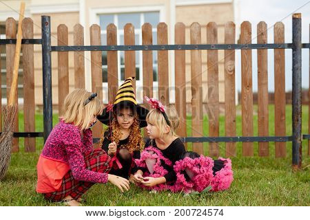 Three girls in traditional halloween costumes playing in the yard by fence