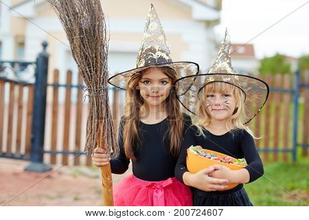 Cute little witches with broom and treats on background of house