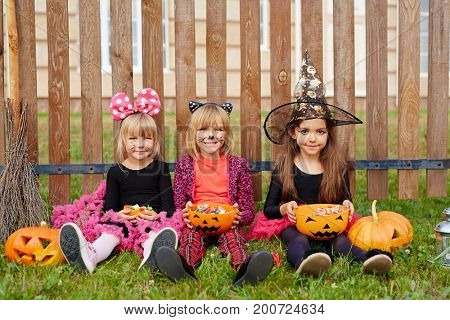 Youthful girls in halloween costumes sitting on grass by fence and eating treats