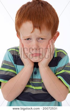 Young Boy Holding Face And Looking Sad