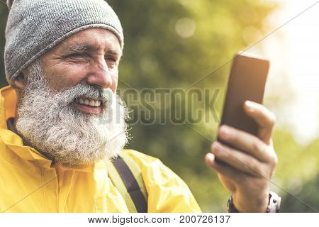 Joyful old man in yellow windbreaker is using smartphone during his trip. He is looking at screen and smiling. Portrait