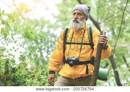 Portrait of serious old man in yellow windbreaker hiking in wild woodland. He is carrying backpack and looking forward pensively. Copy space
