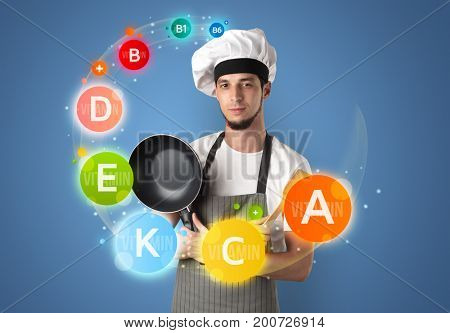 Handsome cook with kitchen instruments and vitamin concept