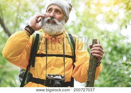 Portrait of pensive senior male tourist talking on mobile phone while traveling in forest. He is standing and leaning on wooden stick