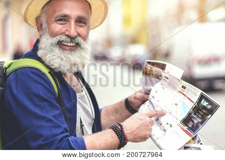 That is the play where I want to go to. Portrait of joyful senior male tourist pointing finger at map and smiling. He is standing on street with backpack