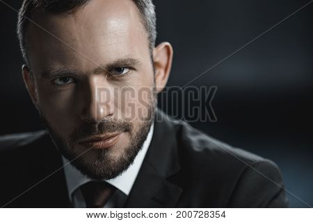 head and shoulders shot of young caucasian businessman looking at camera isolated on black