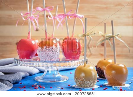 Glass stand with delicious candy apples on table