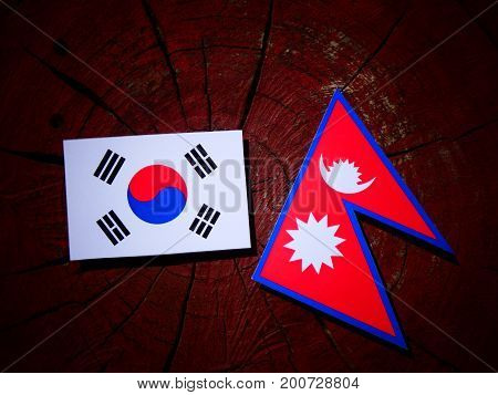 Nepali Flag With South Korean Flag On A Tree Stump Isolated