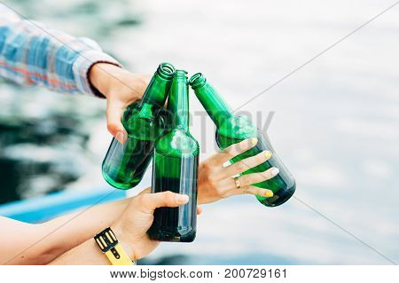 Cheers! Group of young people holding and toasting with green bottles of beer on river background. Celebrating oktoberfest with friends outdoor. Barbecue, hanging out, relaxing concepts.