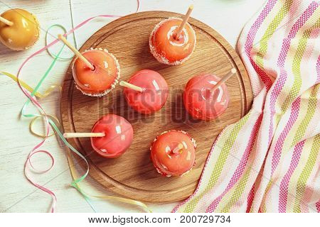 Cutting board with delicious candy apples on table
