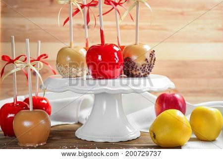 Ceramic stand with delicious candy apples on table