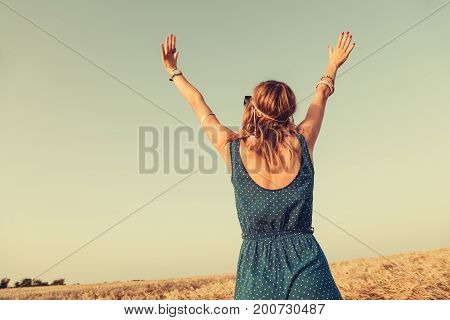 Woman jumping in the nature with arms wide open.
