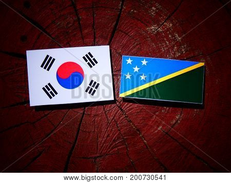 Solomon Islands Flag With South Korean Flag On A Tree Stump Isolated
