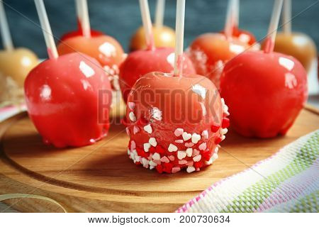 Cutting board with delicious candy apples, closeup