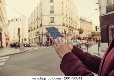 Girl holding cellphone in urban surroundings - shallow depth of field.