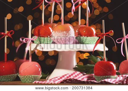 Ceramic stand with delicious candy apples on blurred background