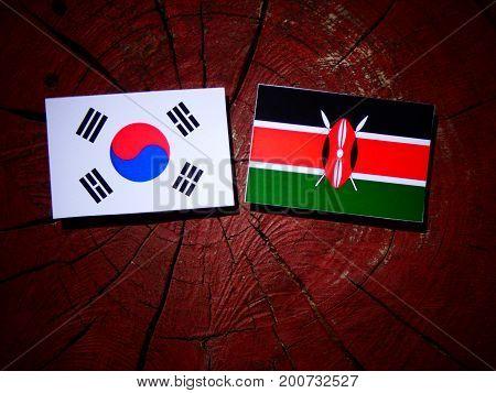 Kenyan Flag With South Korean Flag On A Tree Stump Isolated
