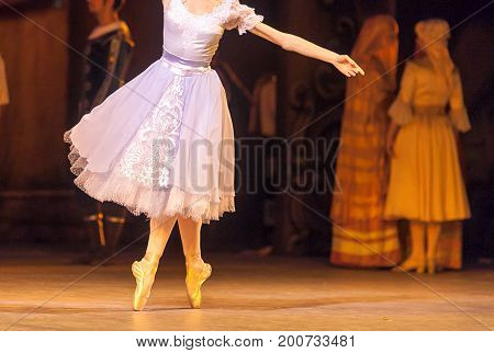 choreography, entertainment, costume concept. enchanting young ballerina wearing tender lilac dress with beautiful lace spinning around the stage on her toes performing solo dance